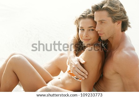 Close up portrait of a young attractive couple sitting down on golden sand sea shore, while on honeymoon vacations. - stock photo