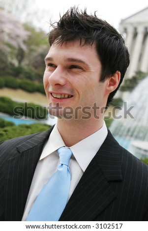 Close-up portrait of a young attractive executive smiling. - stock photo