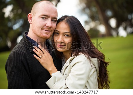 Close up portrait of a young attractive romantic couple, caucasian man, asian woman, in a beautiful outdoor park garden - stock photo
