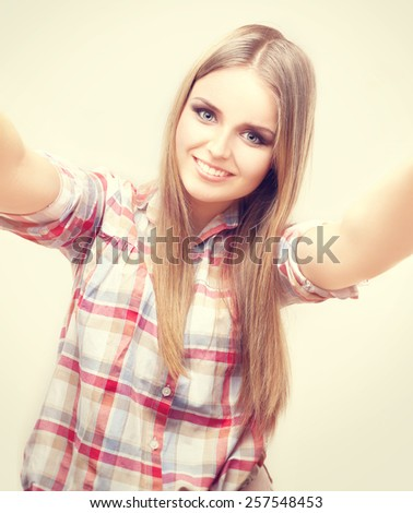 Close up portrait of a young attractive teen girl holding a smartphone digital camera with her hands and taking a selfie. Casual girl in taking a selfie. - stock photo
