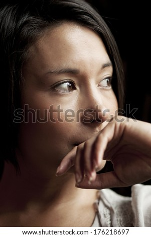Close up portrait of a young attractive woman looking away in thought - stock photo