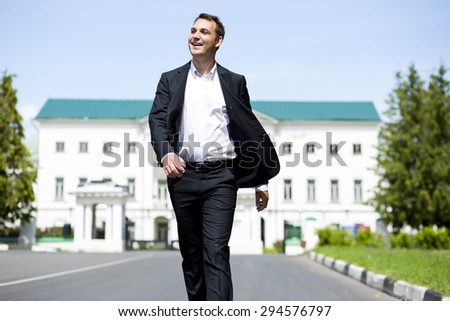 Close up portrait of a young business man in a dark suit and white shirt on the background of summer city - stock photo
