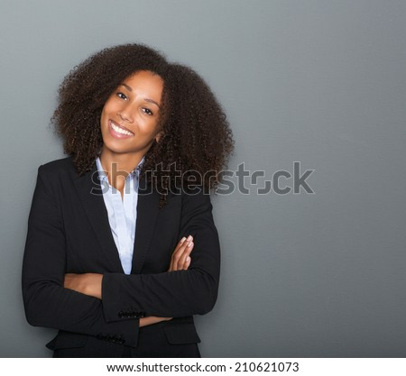 Close up portrait of a young business woman smiling with arms crossed on gray background - stock photo
