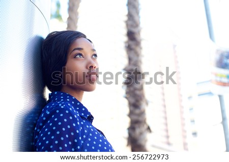 Close up portrait of a young business woman standing outdoors thinking - stock photo