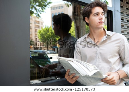 Close up portrait of a young businessman holding a newspaper and standing in the city by a glass window with reflections of office buildings. - stock photo