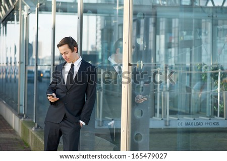 Close up portrait of a young businessman sending message on mobile phone - stock photo