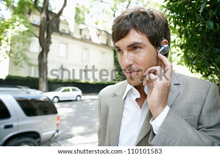 Close up portrait of a young businessman using an ear piece microphone to make a phone call. - stock photo