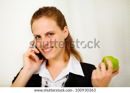 Close up portrait of a young businesswoman speaking on the mobile phone while is eating a green apple - stock photo