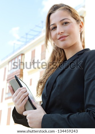 Close up portrait of a young businesswoman standing near classic office buildings in a city, carrying a digital tablet pad and a folder, smiling. - stock photo