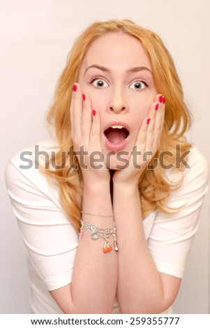 Close up portrait of a young caucusian woman with curly blond hair scared, afraid and anxious. Screaming, with eyes wide open. Human emotions. Parody on a Munch Scream. Isolated on a white background. - stock photo