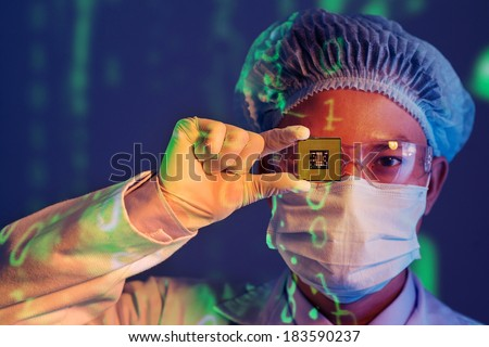 Close-up portrait of a young computer engineer with microchip instead of his eye  - stock photo