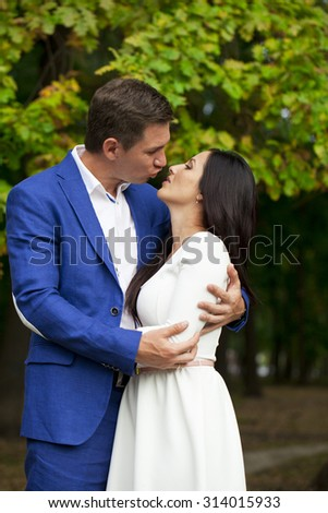 Close up portrait of a young couple kissing on the background of autumn park - stock photo