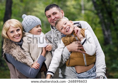 Close up portrait of a young family in the autumn park - stock photo