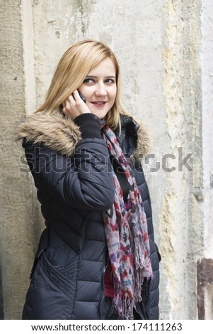 Close up portrait of a young fashionable woman holding a smartphone - stock photo