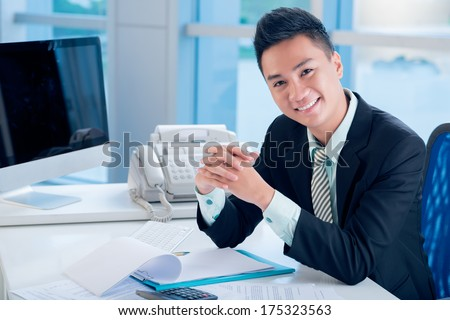 Close-up portrait of a young financial worker smiling and posing at camera  - stock photo