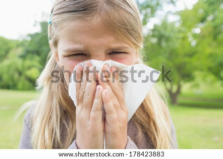 Close-up portrait of a young girl blowing nose with tissue paper at the park - stock photo