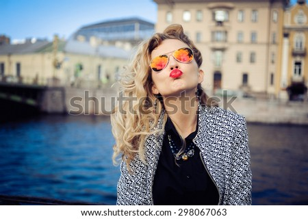 close-up portrait of a young girl hipster beautiful blonde in sunglasses with red lips laughing and posing against the backdrop of the city - stock photo