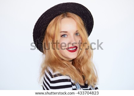 close-up portrait of a young girl hipster blonde in hat and striped shirt with red lips smiling and posing against the isolated white background - stock photo