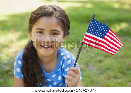 Close-up portrait of a young girl holding the American flag at the park - stock photo