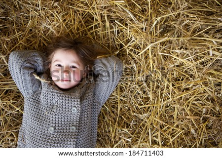Close up portrait of a young girl relaxing on hay and thinking  - stock photo