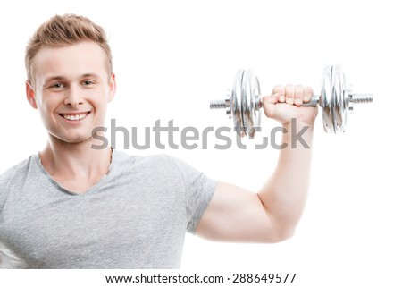 Close up portrait of a young handsome man wearing grey t-shirt standing smiling and holding a silver dumbbell in his hand showing his muscled biceps during training, isolated on white background - stock photo
