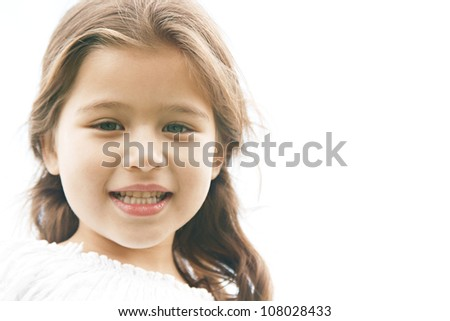 Close up portrait of a young innocent girl child, smiling at camera. - stock photo