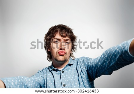 Close up portrait of a young kissing man holding a smartphone digital camera with his hands and taking a selfie self portrait of himself standing against grey background - stock photo