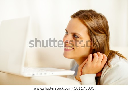 Close up portrait of a young lovely woman lying on sofa and looking to laptop screen while resting - stock photo
