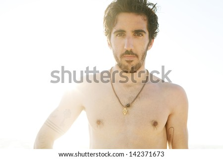 Close up portrait of a young man with beard standing on a beach against the sky with the sun behind him, filtering through his shoulder during the sunset on vacation. - stock photo
