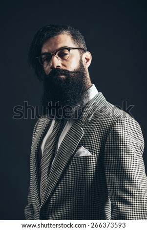 Close up Portrait of a Young Man with Long Facial Hair Wearing Formal Suit with Eyeglasses Looking at Camera Seriously on a Black Background - stock photo