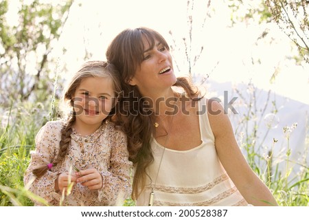 Close up portrait of a young mother and daughter relaxing during a sunny holiday, with their heads together joyfully smiling with fun expressions in a field. Family activities lifestyle, outdoors. - stock photo