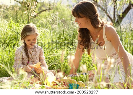 Close up portrait of a young mother and daughter relaxing together having a picnic in a green garden eating healthy food and peeling a banana. Family activities and healthy eating lifestyle, outdoors. - stock photo