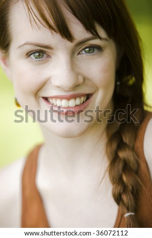 Close-up portrait of a young pretty woman smiling - stock photo