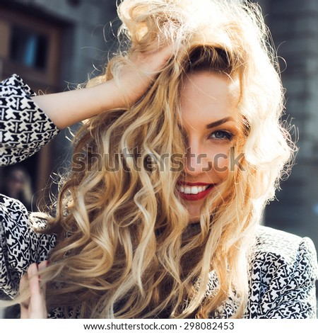 close-up portrait of a young sexy girl hipster beautiful blonde  with red lips laughing and posing against the backdrop of the city - stock photo