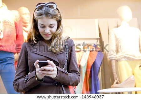Close up portrait of a young stylish teenager woman using a smartphone device while visiting the city, leaning on a fashion store shop window while shopping for clothes. - stock photo