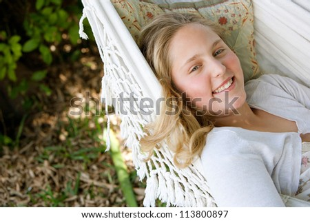 Close up portrait of a young teenage girl laying down on a hammock in a garden, smiling. - stock photo