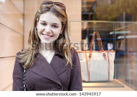 Close up portrait of a young teenager tourist visiting the city during the weekend and leaning on a fashion store window, smiling and being joyful. - stock photo