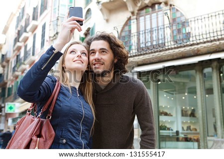 Close up portrait of a young tourist couple visiting a destination city and taking pictures of themselves while on vacation in Europe. - stock photo