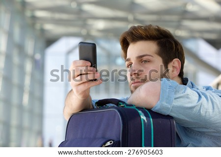 Close up portrait of a young traveling man waiting at station and looking at mobile phone - stock photo