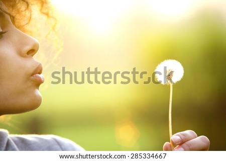 Close up portrait of a young woman blowing dandelion flower outdoors - stock photo