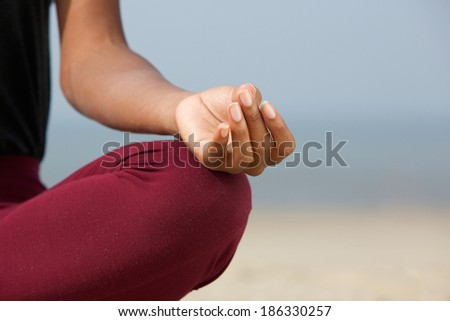 Close up portrait of a young woman in lotus position at the beach  - stock photo