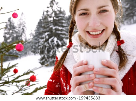 Close up portrait of a young woman in the snow mountains, holding a comforting hot cup of tea or coffee beverage with a decorated christmas tree, warming up in the winter and smiling. - stock photo