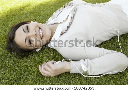 Close up portrait of a  young woman listening to music on her mp4, laying down on green grass in a park and smiling at camera. - stock photo