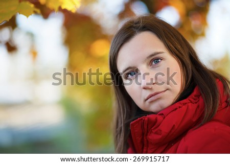 Close-up portrait of a young woman on a colorful bright blurry background of autumn foliage. Shallow depth of field. Focus on the model's face. Space for text. - stock photo