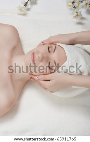 Close up portrait of a young woman receiving facial massage - stock photo