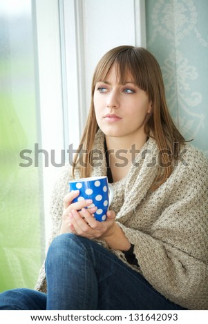 Close up portrait of a young woman relaxing with cup of tea - stock photo