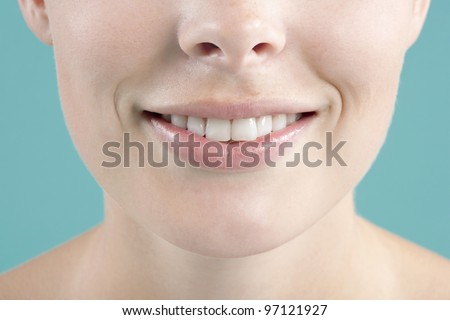 Close up portrait of a young woman's smile against a blue background. - stock photo