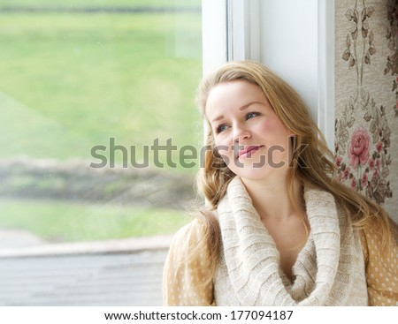 Close up portrait of a young woman sitting by window looking outside - stock photo