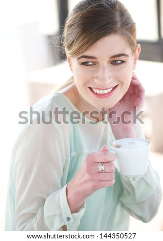 Close up portrait of a young woman smiling and enjoying a cup of coffee outdoors - stock photo