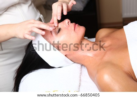 Close up portrait of a young woman with eyes closed receiving facial massage - stock photo
